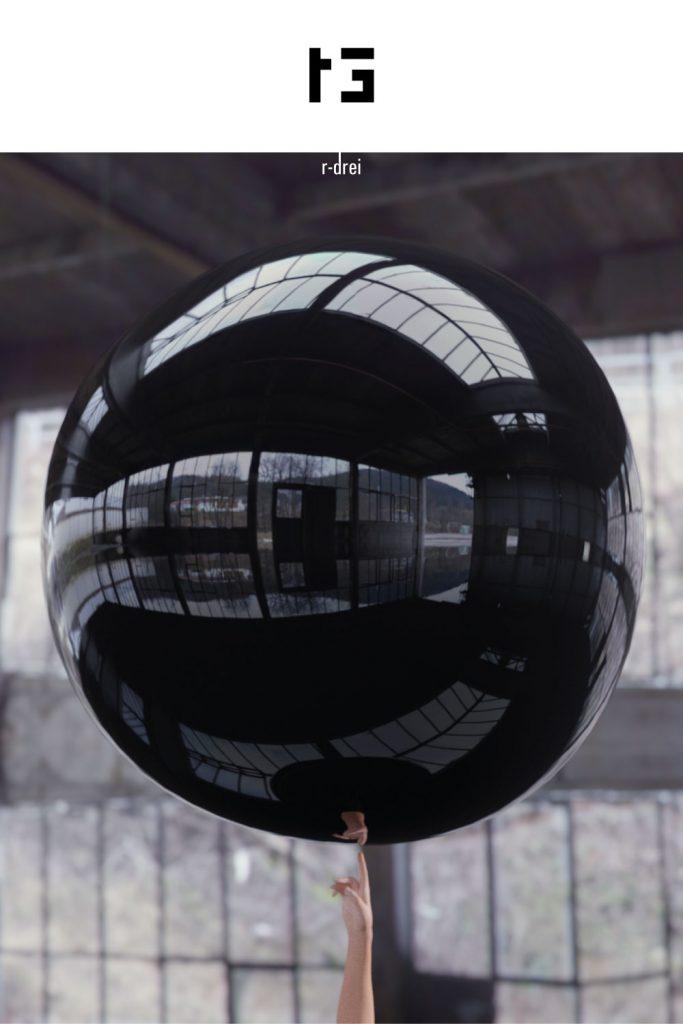 schwebender schwarzer Ballon über Fingerspitze als Beispiel für motion graphics